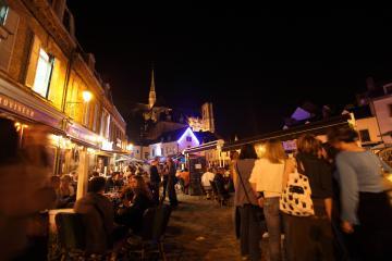 Vue de nuit sur la place du Don dans le quartier Saint-Leu.Des personnes boivent un verre en terrasse.