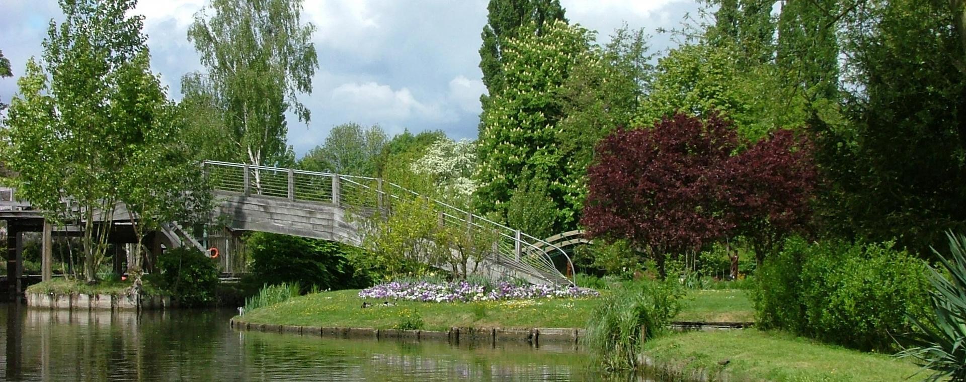 Vu les canaux des Hortillonnages. En arrière plan une passerelle en bois enjambant le canal.