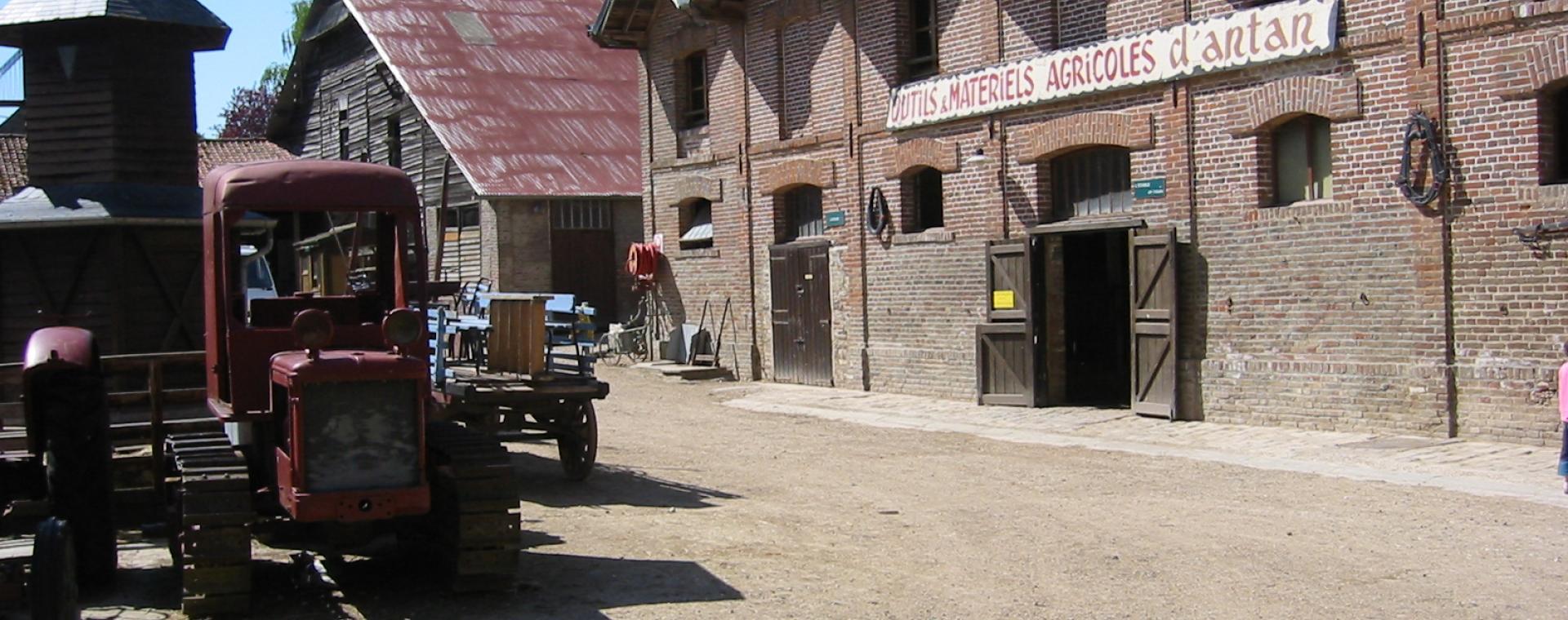 Photo de la cours de la ferme d'antan à Creuse avec un tracteur stationné sur le bas côté.