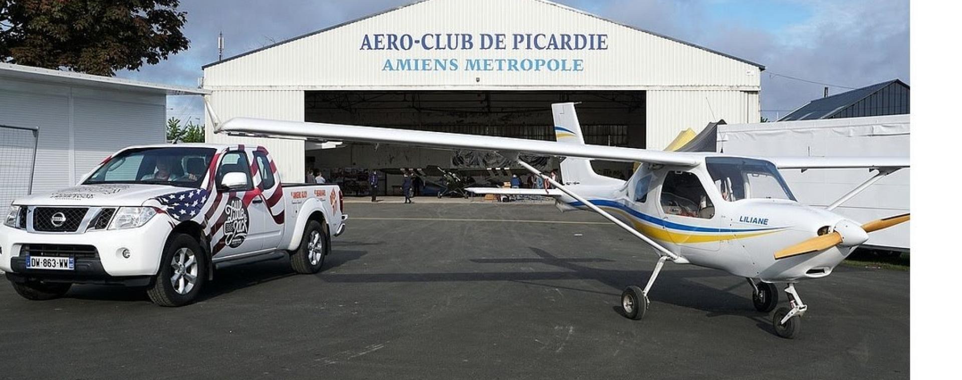 Photo du hangar de l'aéroclub de Picardie à Glisy. Un avion et une voiture sont stationnés en extérieur.