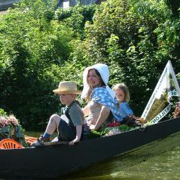 Barque traditionnelle des hortillonnages d'Amiens avec une mère et ses enfants en costume traditionnel à l'occasion du marché sur l'eau.