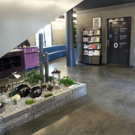 Photo d'une partie de l'intérieur de l'Office de Tourisme. On y voit le parterre végétal.