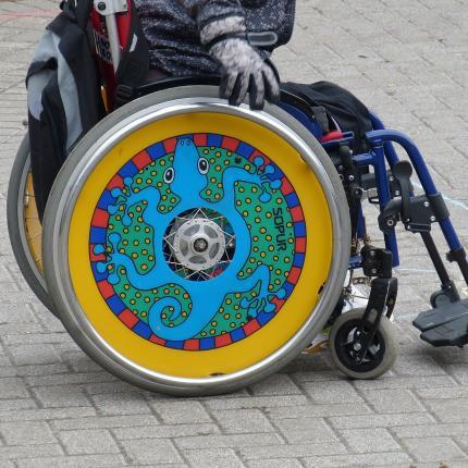 Photo d'un fauteuil roulant aux roues pleines et colorées.