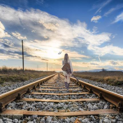Photo d'une voyageuse marchant sur des rails