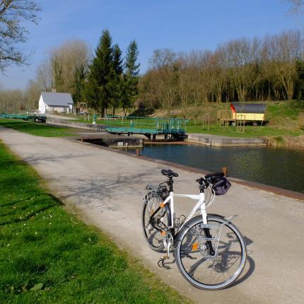 Vue le chemin de halage à Lamotte Brebières. Un vélo est stationné sur le chemin.