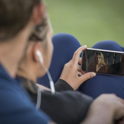 Photo d'un homme assis regardant une vidéo sur son smartphone.