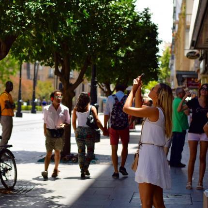 Photo d'une rue avec de nombreux passants. Au premier plan, une femme prenant une photo d'un point d'intérêt dans la ville.