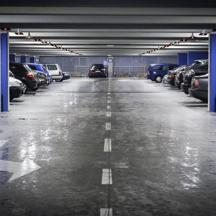 Photo d'un parking souterrain avec des voitures de stationnées de part et d'autres