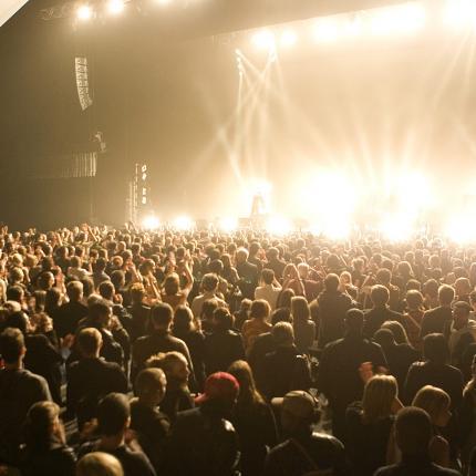 Photo d'un concert au zénith d'Amiens. On y voit la fosse pleine de spectateurs et les projecteurs éclairant la scène.