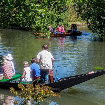 Photo d'un groupe de personnes en visite sur une barque dans les Hortillonnages d'Amiens